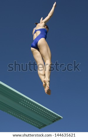 Low angle view of a female swimmer jumping on diving board against clear blue sky - stock photo
