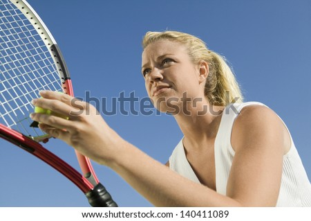 Low angle view of a female tennis player preparing to serve against clear blue sky - stock photo