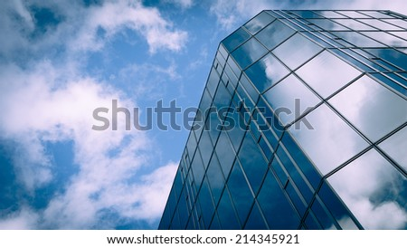 Low angle view of a glass and steel skyscraper blending into and reflecting the blue sky and clouds. - stock photo