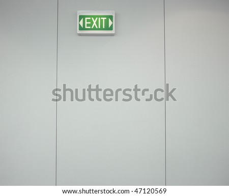 Low angle view of a green, lighted exit sign on a gray wall. Horizontal shot.