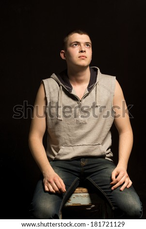 Low angle view of a handsome muscular fit young man sitting thinking staring pensively up into the air on a dark background - stock photo