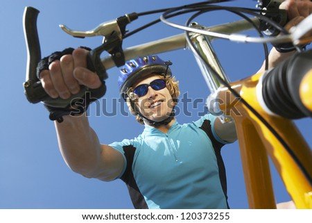 Low angle view of a happy young male cyclist riding bicycle against blue sky