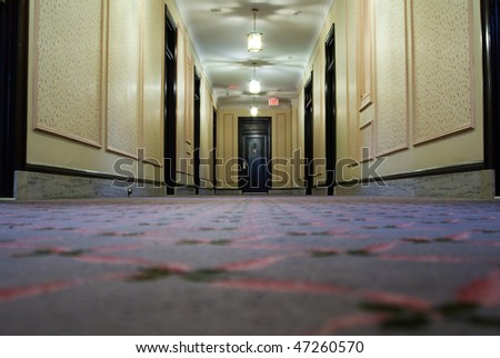 Low angle view of a hotel hallway with a doors on the side and at the end. - stock photo