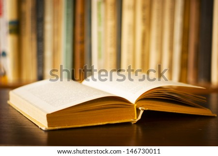Low angle view of a large open hardcover book lying on a wooden desk in front of a shelf of books with shallow dof - stock photo