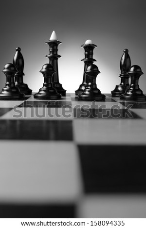 Low angle view of a line of backlit chess pieces on a chessboard with pawns, king , queen and bishops