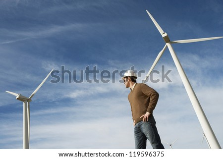 Low angle view of a male engineer against wind turbine and cloudy sky