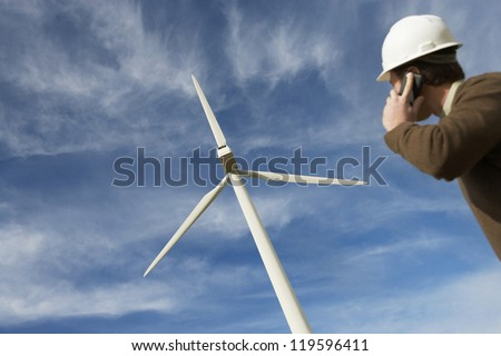 Low angle view of a male engineer on call while looking at the wind turbine against cloudy sky