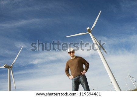 Low angle view of a male engineer standing against wind turbine and cloudy sky