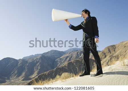 Low angle view of a middle aged businessman yelling through megaphone against clear sky - stock photo