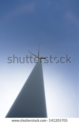 Low angle view of a modern wind turbine with bright blue sky in the background.