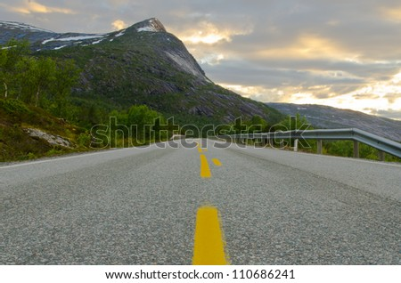 Low angle view of a road with a steep mountain as background - stock photo