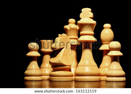 Low angle view of a set of different chess pieces in a light coloured wood standing on a reflective wooden surface against a black background - stock photo