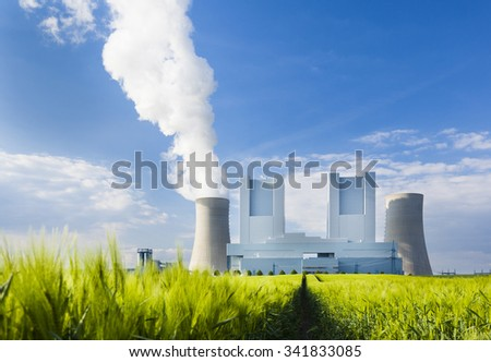 Low angle view of a shiny new lignite power station behind a rye field with wheel tracks leading to it. Focus on the power station.