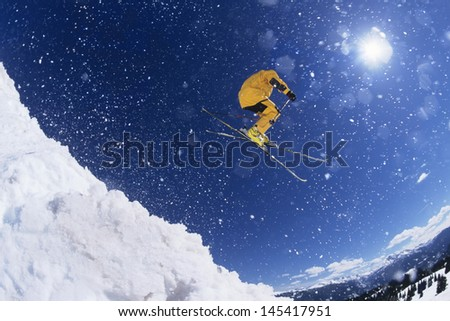 Low angle view of a skier in midair above snow on ski slopes - stock photo
