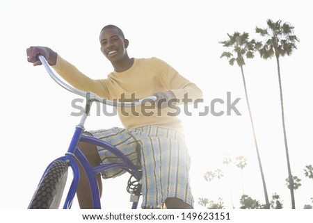 Low angle view of a smiling man with bike on beach - stock photo
