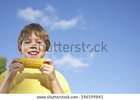 Low angle view of a smiling young boy eating corn on the cob against sky