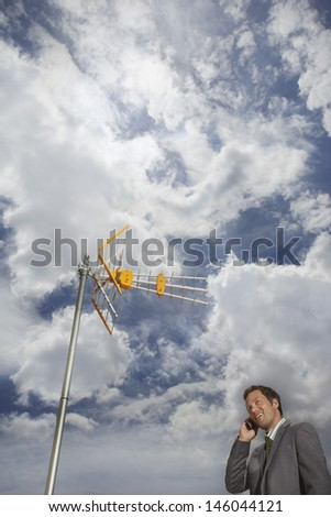 Low angle view of a smiling young businessman using cellphone under satellite tower and against cloudy sky - stock photo