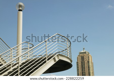 Low angle view of a staircase with a high-rise in the background - stock photo