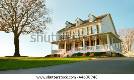 Low angle view of a traditional upscale home with a single tree in the front yard. Horizontal format. - stock photo