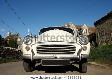Low Angle View of a Vintage Car on a Country Road - stock photo
