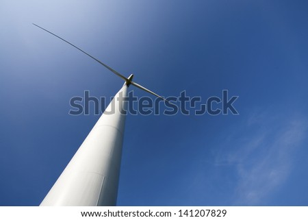 Low angle view of a wind turbine with blue sky at the back.
