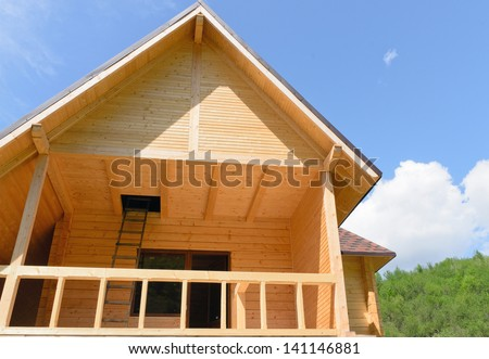 Low angle view of a wooden chalet or cabin with a balcony and stepladder going up into the loft