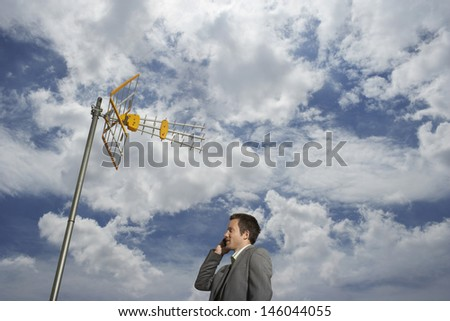 Low angle view of a young businessman using cellphone under satellite tower and against cloudy sky - stock photo