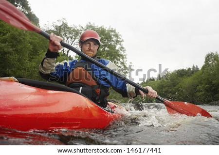 Low angle view of a young man kayaking in river - stock photo