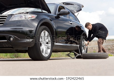 Low angle view of a young man with a roadside puncture changing the tyre on his car for his spare on a country road - stock photo