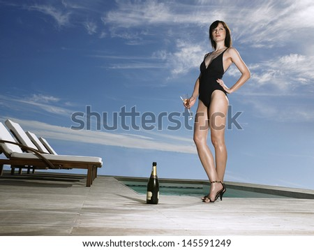 Low angle view of a young woman in bathing suit holding champagne at poolside - stock photo