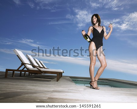 Low angle view of a young woman in bathing suit holding champagne bottle at poolside - stock photo