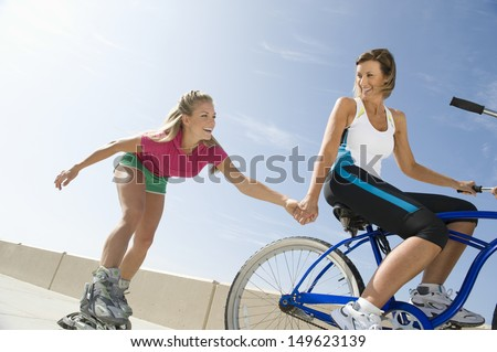 Low angle view of a young woman on bike pulling friend on in-line skates - stock photo