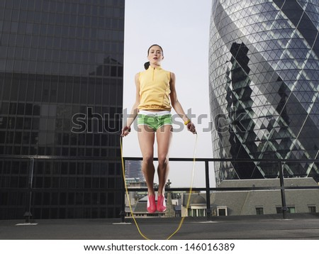 Low angle view of a young woman skipping against downtown buildings in London - stock photo