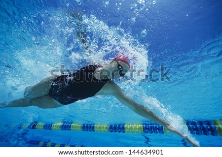 Low angle view of a young woman swimming underwater - stock photo