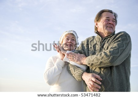 Low angle view of affectionate happy mature couple arm in arm outdoors - stock photo
