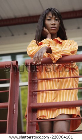 Low angle view of African woman on balcony - stock photo