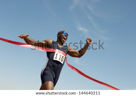 Low angle view of an African American male runner winning race against blue sky - stock photo