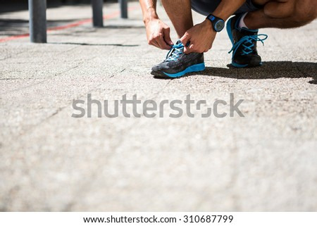 Low angle view of an athletic man tying his shoe laces - stock photo