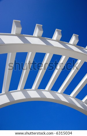 Low angle view of arched white trellis with blue sky. - stock photo