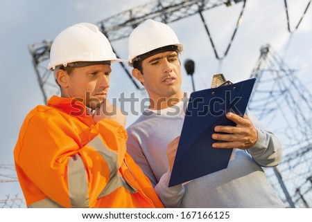 Low angle view of architects discussing over clipboard - stock photo