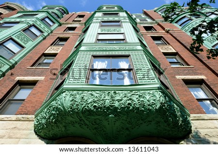 Low angle view of bay windows in a Back Bay, Boston mansion. Strong perspective and lots of carving details in verdigris copper awning. - stock photo