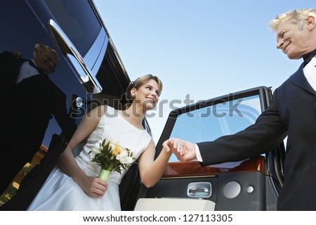 Low angle view of beautiful bride getting down from car while holding father's hand - stock photo