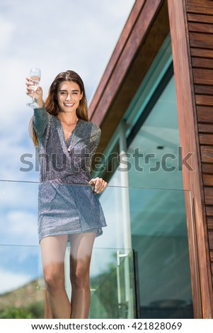 Low angle view of beautiful woman showing champagne flute while standing by glass railing at balcony