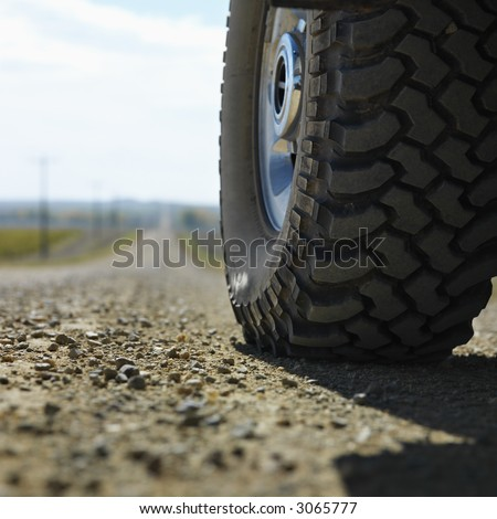 Low angle view of big truck tire on gravel road in rural South Dakota. - stock photo