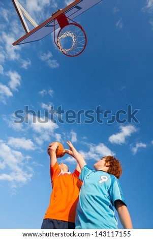 Low angle view of boys playing basketball against sky - stock photo