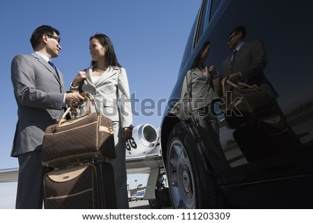 Low angle view of business couple standing together by car at airfield - stock photo
