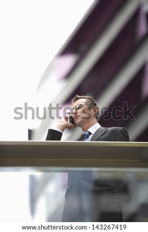 Low angle view of businessman communicating on mobile phone in front of railing - stock photo