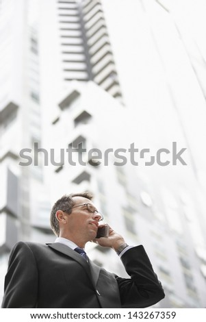 Low angle view of businessman on call against tall building - stock photo