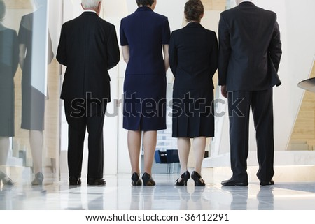 Low angle view of businesspeople standing in a corridor. - stock photo
