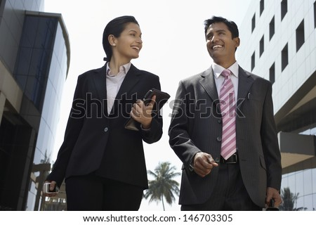 Low angle view of businesswoman and businessman walking outdoors